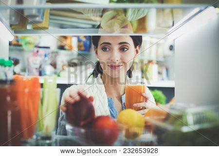 Portrait of female standing near open fridge full of healthy food, vegetables and fruits