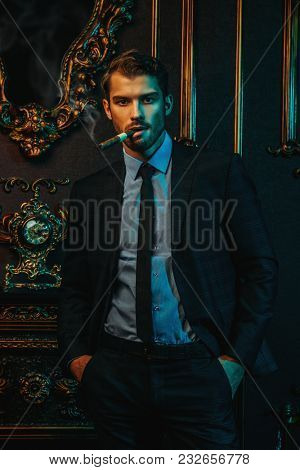 Portrait of an imposing man in an expensive suit smoking a cigar. Men's beauty, fashion. Luxury apartments with classical vintage interior.