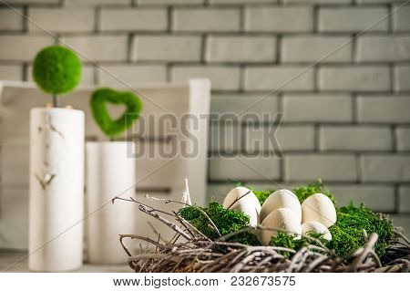 Beautiful White Light Easter Photo. Eggs Of Concrete Lie In A Wreath And Moss. Concrete Vases In The