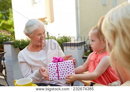 family, generation and people concept - granddaughter giving present to happy grandmother at cafe or restaurant