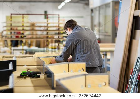 production, manufacture and industry concept - assembler working making furniture at factory workshop