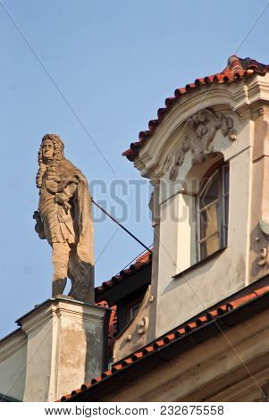 The Figure Of A Man In A Wig That Looks Like A King On The Top Of A Building