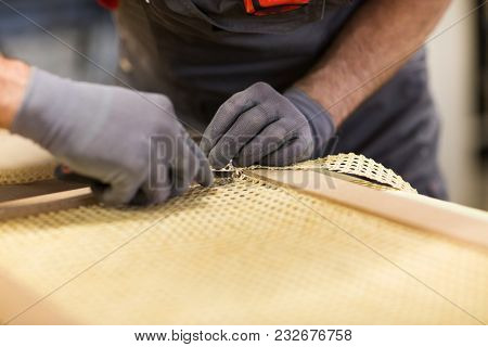 production, manufacture and industry concept - assembler with cutter or knife making furniture