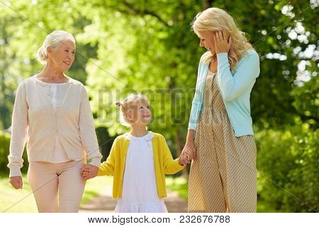 family, generation, women and people concept - happy smiling mother with daughter and grandmother walking at summer park