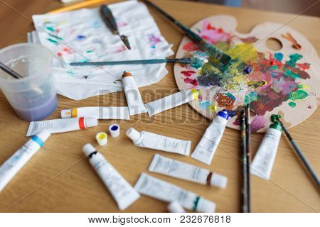 fine art, creativity and artistic tools concept - palette, brushes and paint tubes on table