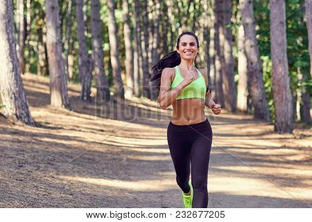 A Girl Jogging In The Woods Outdoors. Healthy Lifestyle.