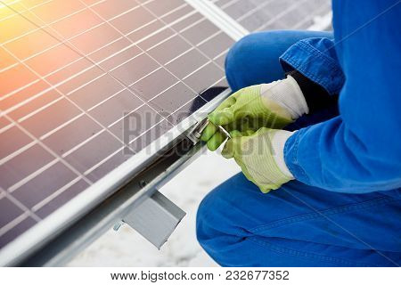 Technician In Blue Suit Installing Blue Solar Panels With Screw. Photovoltaic Modules As Renewable E