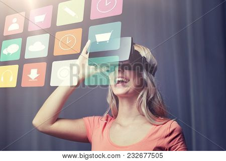 technology, virtual reality, cyberspace, entertainment and people concept - happy young woman with virtual reality headset or 3d glasses at home looking at menu icons projection