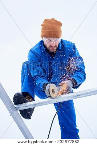 Upward Shot Of Male Technician In Blue Suit Cutting Metal With Cutting Wheel In Order To Install Pho