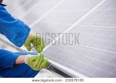 Male Technician In Blue Suit Installing Photovoltaic Blue Solar Modules With Screw. Renewable Energy