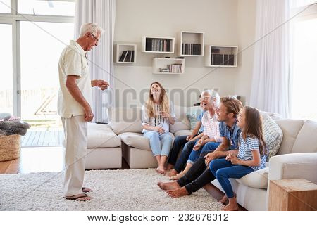 Multi Generation Family Sitting On Sofa At Home Playing Charades