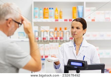 medicine, pharmaceutics, health care and people concept - apothecary giving analgetic drug to senior man customer with headache at drugstore
