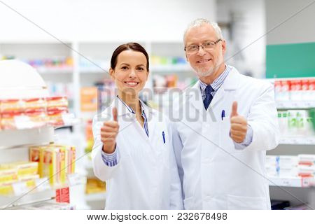 medicine, healthcare and technology concept - happy smiling apothecaries at pharmacy showing thumbs up