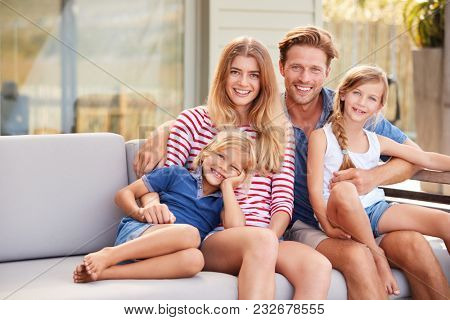 Portrait Of Family Relaxing On Deck At Home