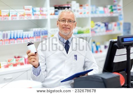 medicine, healthcare and people concept - senior apothecary with drug at pharmacy cash register