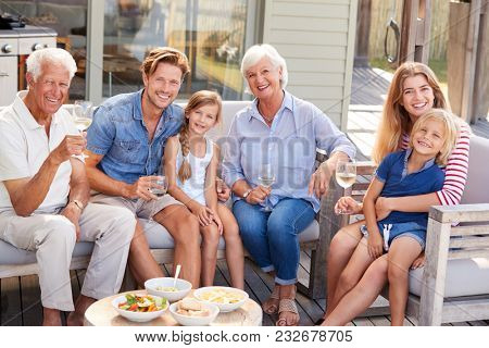 Portrait Of Multi Generation Family Enjoy Outdoor Drinks At Home