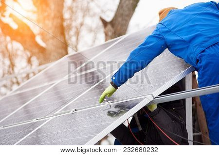 Process Of Mounting Blue Solar Modules On The Roof Of Modern Building During Winter Snowy Time. Team