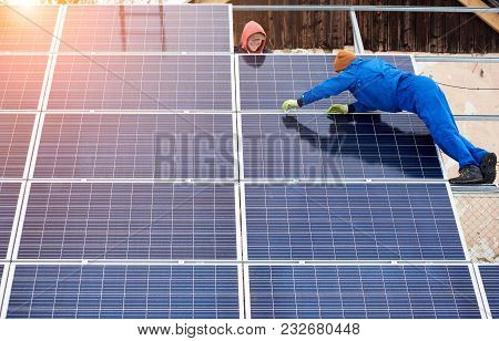 Team Work. Group Of Professionals Mounting Photovoltaic Solar Modules On Roof Top During Winter Time