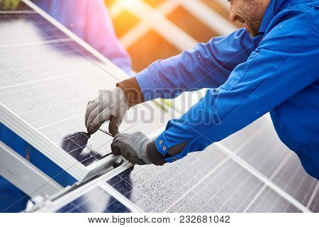 Smiling Male Technician In Blue Suit Installing Photovoltaic Blue Solar Modules With Screw. Man Elec