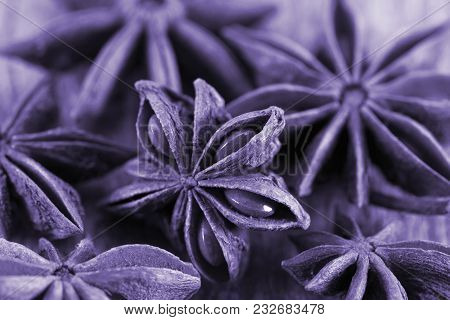 Star Anise On A Wooden Background. Toning In Pantone Color - Ultra Violet. Macro.