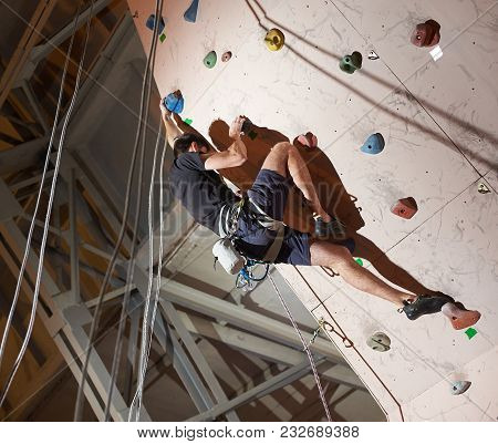 Muscular Man Practicing Rock-climbing On A Rock Wall Indoors. The Concept Of Sport And Health At Any