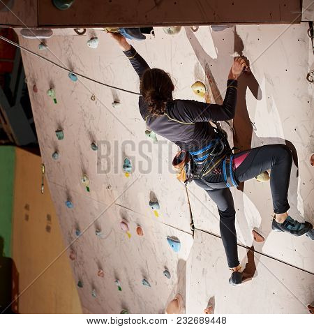 Young Sporty Woman Reaching The Top Of Artificial Bouldering Wall While Exercising In Bouldering Gym