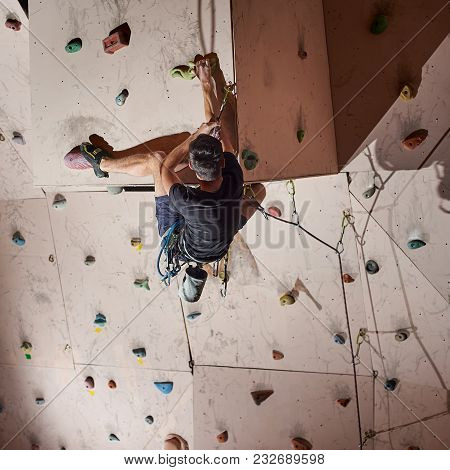 Rear View Of Muscular Man Practicing Rock-climbing On A Rock Wall Indoors. The Concept Of Sport And
