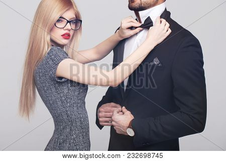 Sexy Young Woman With Red Lips Tying Bow Tie For Stylish Rich Man