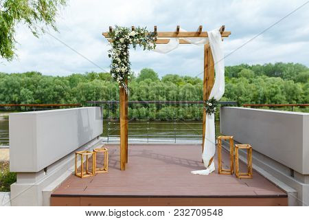 Area Of The Wedding Ceremony Near River On The Pier. Wooden Rectangular Arch, White Chairs Decorated