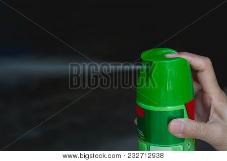 Hand Holding Mosquito Spray. Human Using Mosquito Spray From Bottle.
