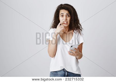 What Shall I Write Back. Portrait Of Worried Anxious Attractive Woman With Curly Hair In Casual Outf