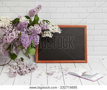 Beautiful Bouquet Of White And Violet Lilac Flowers In Glass Vase With Opened Pad And Black Chalkboa