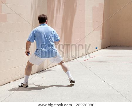 Mid adult man playing racquetball on a public court.
