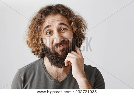 It Would Be Problematic. Portrait Of Hesitating Unsure Eastern Man Scratching Beard And Lifting Eyeb