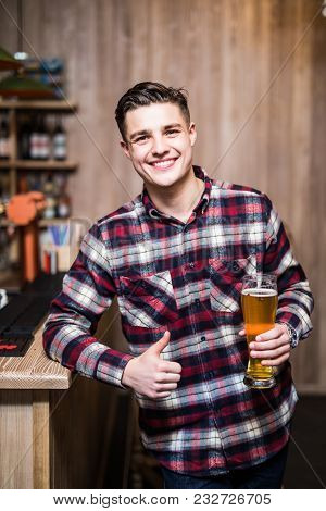 Handsome Man Holding A Pint Of Beer With Thumbs Up In A Pub