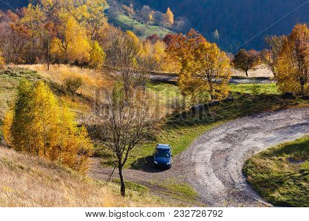 Unrecognizable Car On Dirty Secondary Road To Mountain Pass In Autumn Carpathian Mountains And Multi