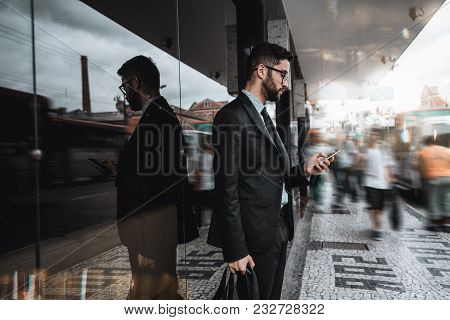 Handsome Young Caucasian Bearded Man Employer In A Formal Suit Is Standing Next To A Bus Stop And Te