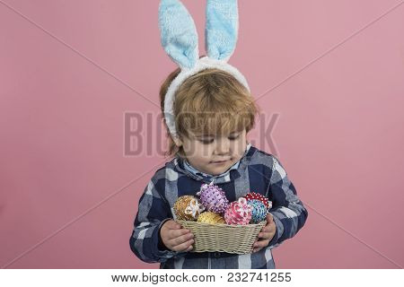 Colorful Eggs Easter Present. Blonde Child Carefully Hold Bowl Of Eggs On Pink Background. Little Bo