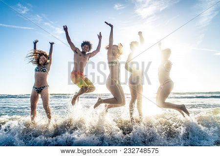 Multi-ethnic Group Of Friends Running On The Beach - Young People Having Fun In The Sea During Summe