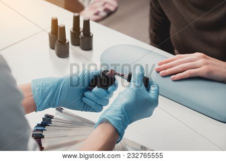 Close up manicurist hand keeping nail lacquer. She preparing paint nails of visitor poster