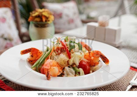 Starter with fried shrimps and raw vegetables, light summer dish, restaurant table outdoors, toned image