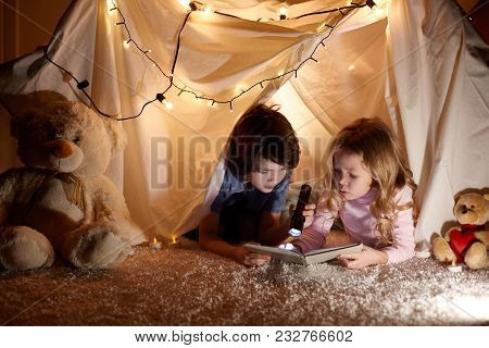 Little Kids Involving In Reading Amazing Book. They Lying In Nice Toy Tent In Playroom. Boy Holding