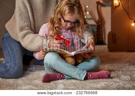 Mother And Kid Interested In Excited Book Together. They Are Sitting On Carpet In Cozy Nursery At Ho