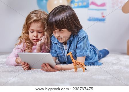 Portrait Of Enthusiastic Boy And Girl Lying On Floor In Playroom And And Watching Modern Tablet. Con
