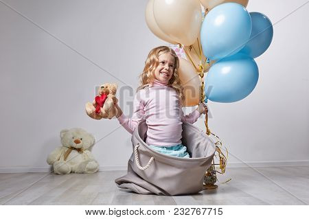 Joyful Laughing Girl Toying With Teddy And Balloons. Concept Chilhood