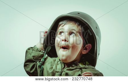 Cute little toddler boy, playing at home with playing wars and peace,funny child dressed in militar hat and goggles