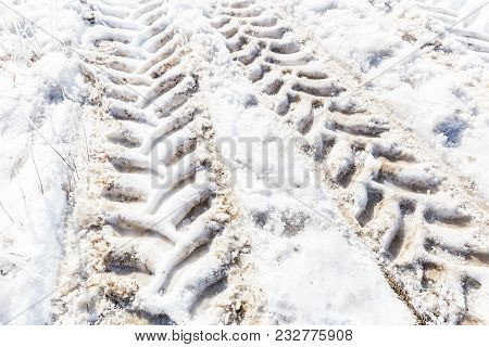 Horizontal Close Up Image Of Big Semi Truck Tire Tracks  In The Snow.