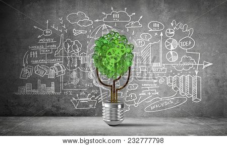 Lightbulb With Tree From Gears Inside Placed Against Business Analytical Information Sketched On Gre