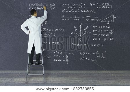 Scientist Of Genius Standing On A Ladder Writing Complex Mathematical Formulas With White Chalk On L