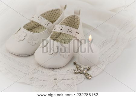 Christening Booties Invitation Background With White Lace, Candle And Crystal Cross Pendant